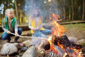 Two girls roasting hotdogs on sticks at bonfire. Children having fun at camp fire.
