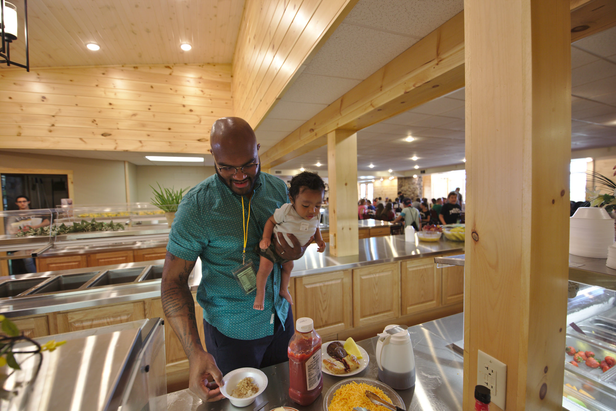 Man with child eating in dining hall